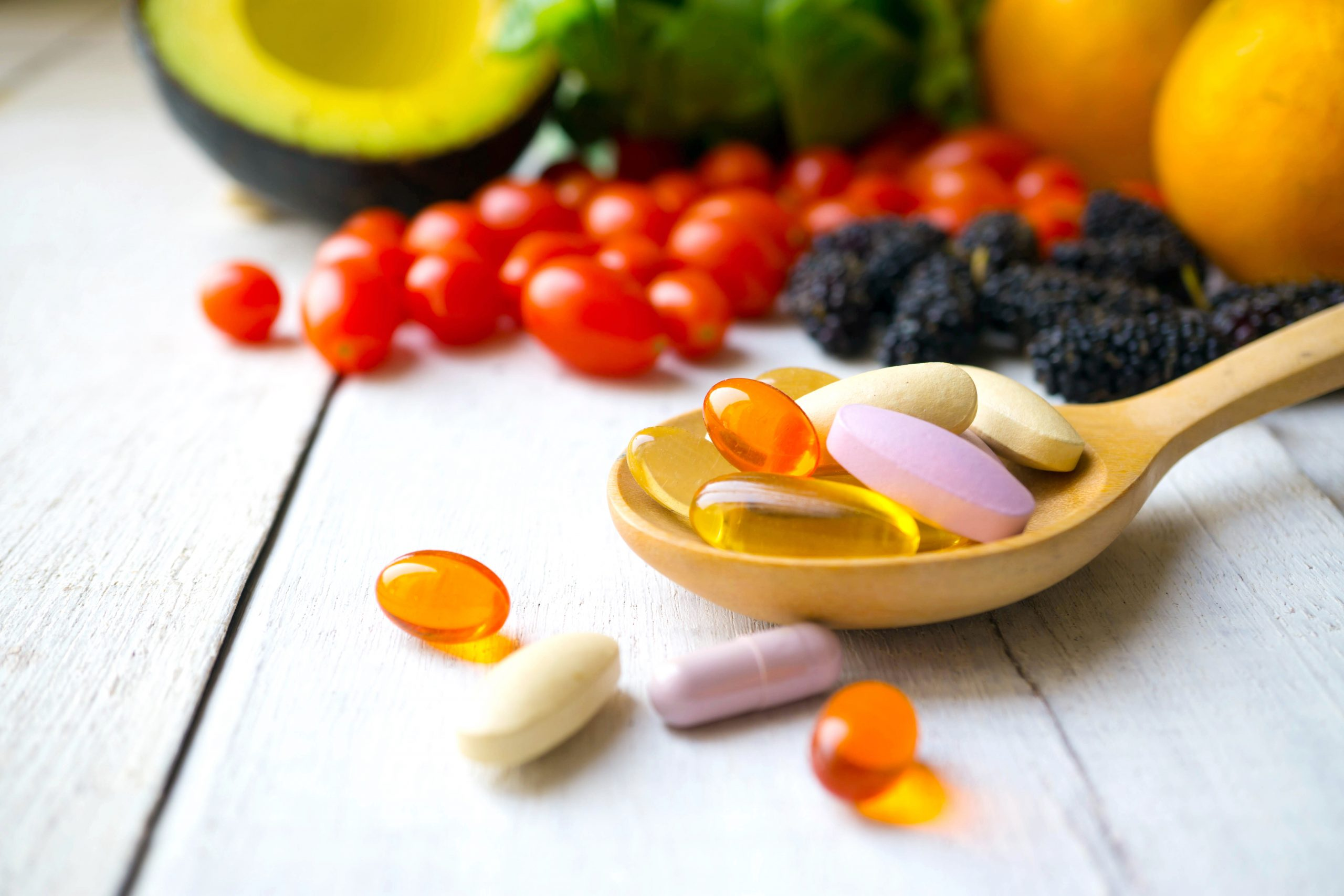 Pills,And,Capsules,In,Wooden,Spoon,With,Fresh,Fruits.multivitamins,And